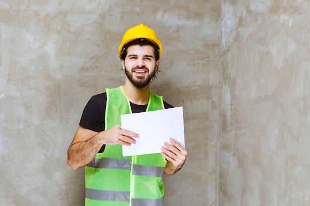 Uomo con casco giallo e attrezzatura che tiene i rapporti sul progetto