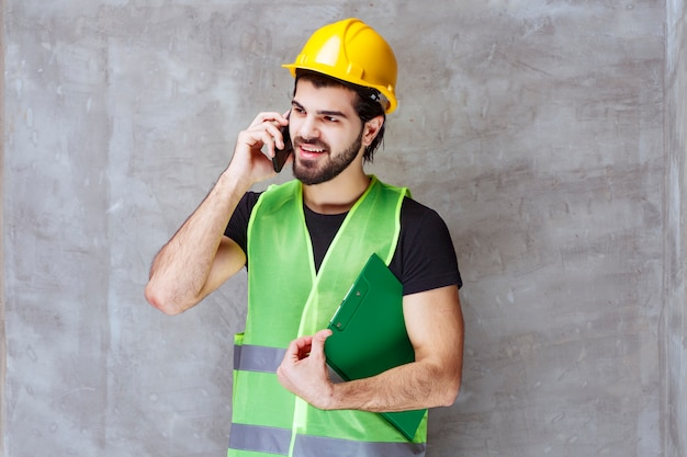 Uomo con casco giallo e attrezzatura che tiene in mano una cartella di rapporti e parla al telefono