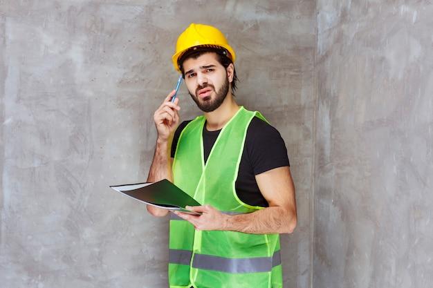 Uomo con casco giallo e attrezzatura che verifica la cartella dei rapporti e sembra pensieroso
