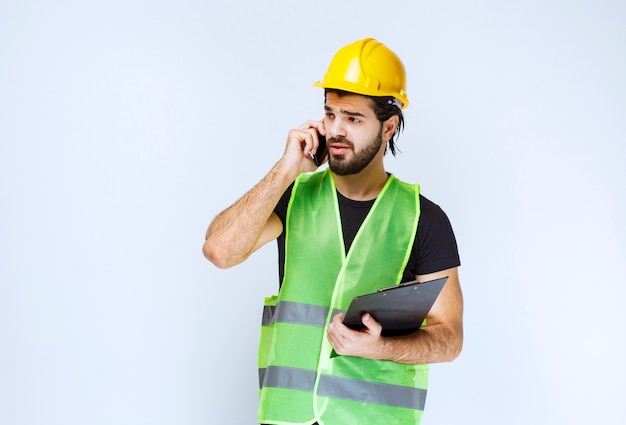 Man in yellow helmet talking to the phone.