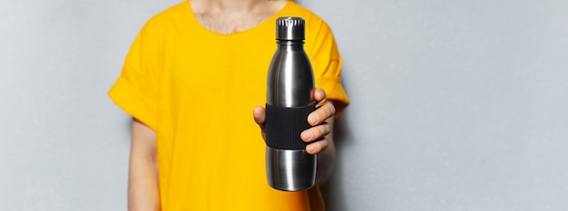 Man in yellow holding steel reusable thermo water bottle on grey background. panoramic banner view.