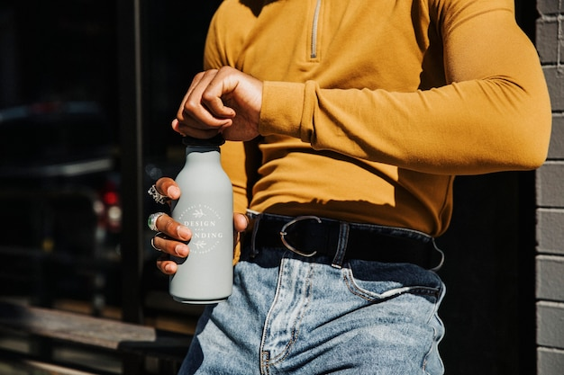 Man in a yellow long sleeve top opening a gray stainless steel tumbler bottle mockup