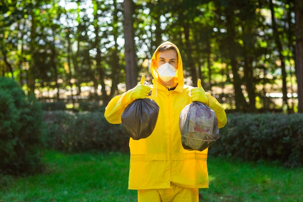 A man in a yellow protective suit and mask holds bags of garbage and shows class with his hands