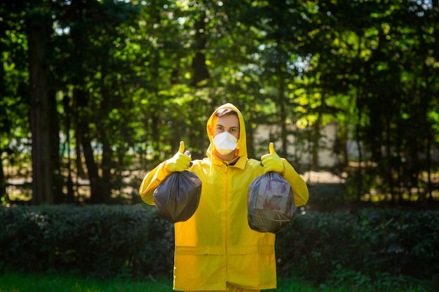 A man in a yellow protective suit and mask holds bags of garbage and shows class with his hands.