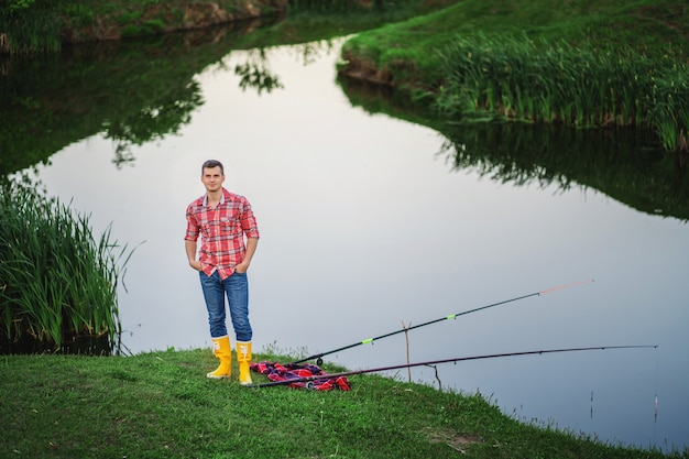 A man in yellow rubber boots and a plaid shirt looks into the frame