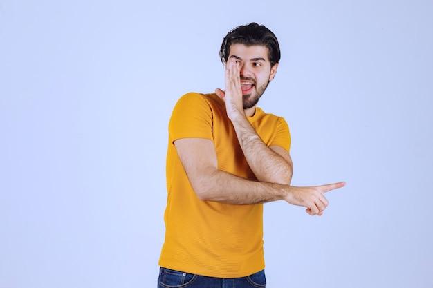Uomo in camicia gialla che fa pettegolezzi.