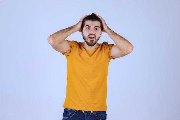 Uomo in camicia gialla che dà pose seducenti e accattivanti.