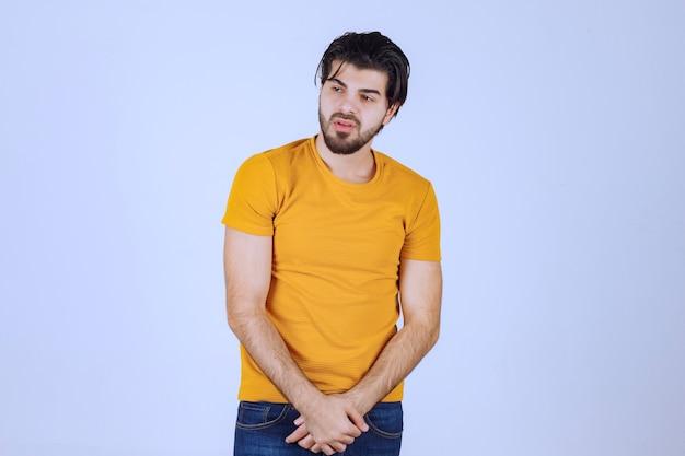 Uomo in camicia gialla che dà pose seducenti e attraenti