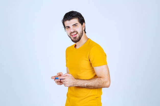 Man in yellow shirt holding a blue smartphone.