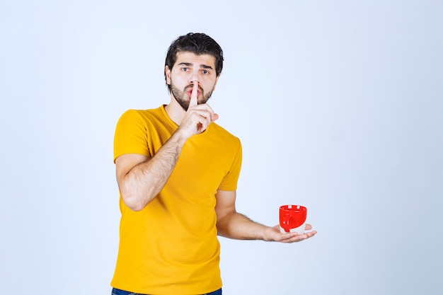 Man in yellow shirt holding a cup of coffee and looks mysterious.
