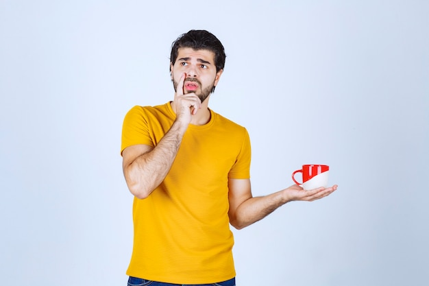 Man in yellow shirt holding a red cup and thinking.