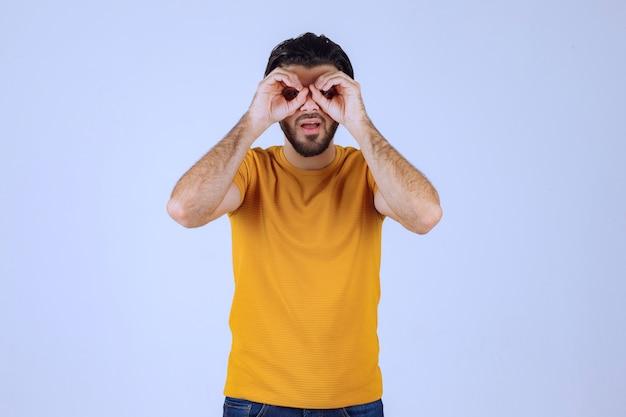 Uomo in camicia gialla che guarda avanti.