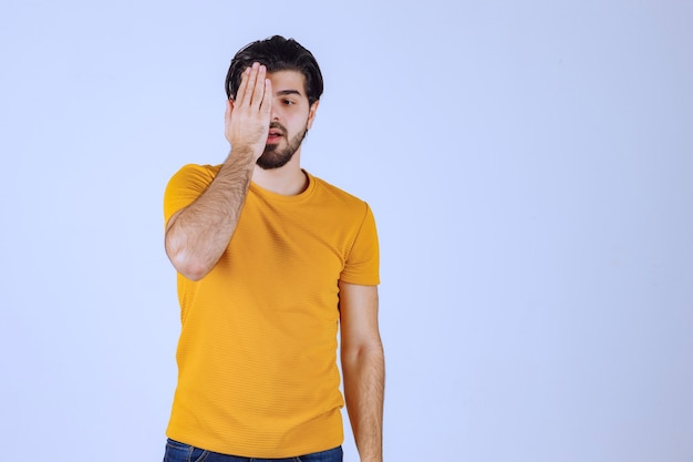 Man in yellow shirt looking through his fingers.