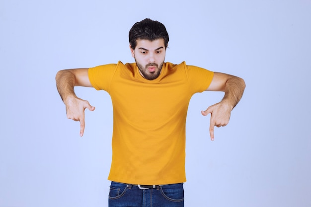 Man in yellow shirt pointing below.