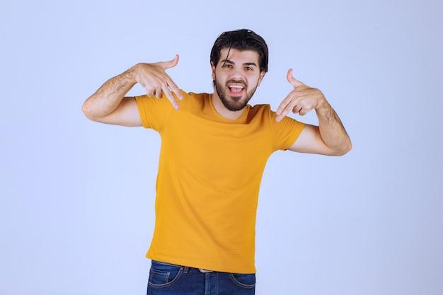 Man in yellow shirt showing gun sign in the hand
