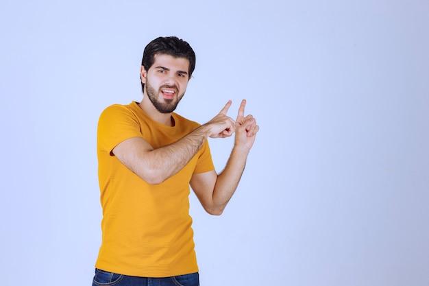 Uomo in camicia gialla che mostra qualcosa sopra.