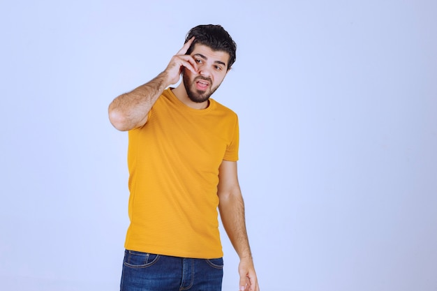 Man in yellow shirt standing neutral without reaction