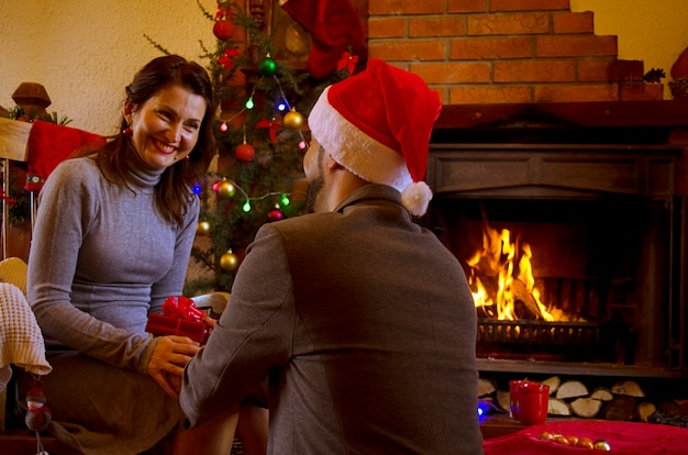 Man and young woman on christmas eve at home by the fireplace.romantic couple celebrate ne