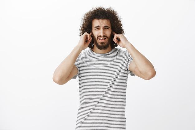 男、あなたのプレーはひどいです。ひげとアフロの髪型、眉をひそめている、人差し指で耳を覆っている、不快な不快な魅力的なヒスパニック男の肖像