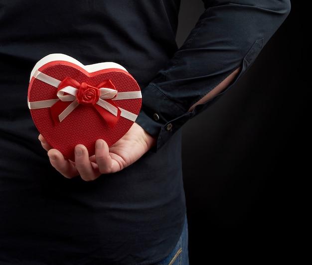 Manã¢â€™™の手は、背中の後ろに弓が付いた段ボールの赤い箱を持っています。