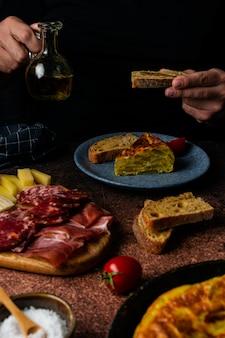 Рука человека, держащая ломтик хлеба с оливковым маслом на тарелке, тарелка с традиционным испанским картофельным омлетом
