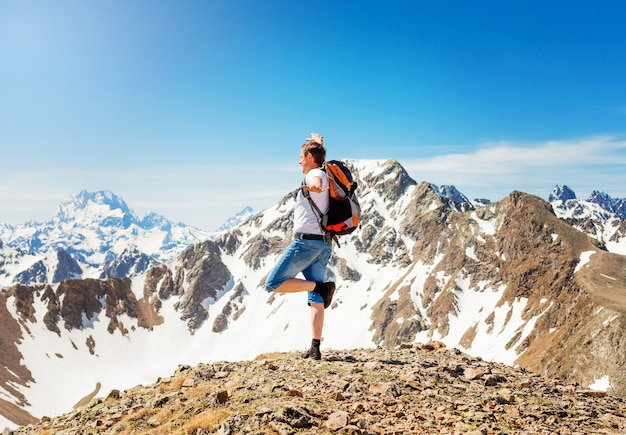 Man's hike to the top of the mountain, success, winner, a man with a backpack stands on top of the mountain. mountains of karachay-cherkessia.