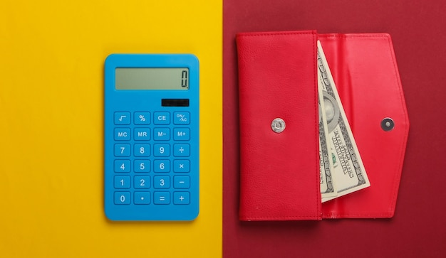 Manage family budget. shopping costs. blue calculator and red leather wallet with dollar bills on yellow red