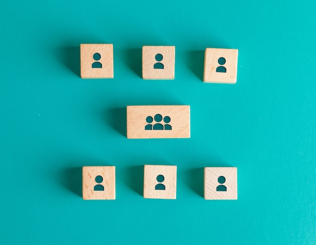 Management structure concept with people icons on wooden blocks on turquoise table flat lay.