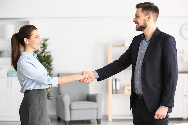 Менеджер и клиент, пожимая руки в офисе