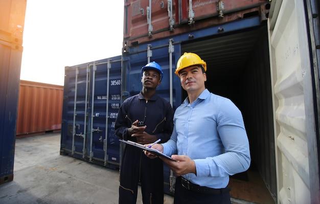 港湾コンテナ船の倉庫文書について話し合っているマネージャーと港湾労働者は、安全制服のヘルメット、フェイスマスクを着用し、無線通信を行っています。