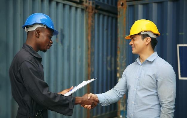Диспетчер и док-рабочий обсуждают документ, подтверждающий отгрузку контейнеров в док, они носят защитную каску, маску и проводят радиосвязь.