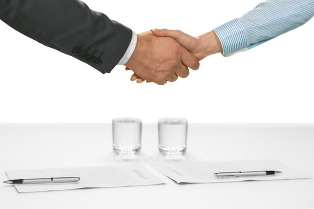 관리자와 직원이 악수합니다. 새로운 동맹을 환영합니다. 팀에 새 구성원이 있습니다. 회사는 더 강해지고 있습니다.