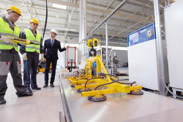 Менеджер и рабочие возле подъемного устройства для листового металла на заводе