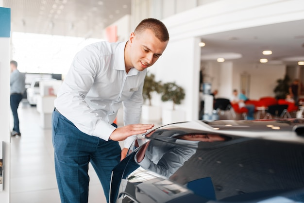 Manager checks the quality of new car paintwork in showroom. male customer buying vehicle in dealership, automobile sale, auto purchase