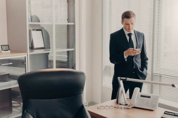 Manager in corporate clothing browses web pages and chats online with smart phone