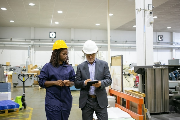 Manager discussing factory work with worker