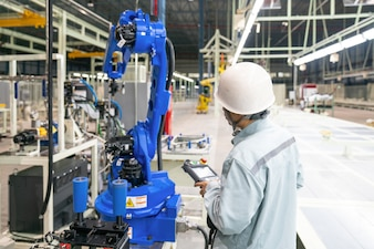Manager engineer check and control automation robot arms machine in intelligent factory industrial
