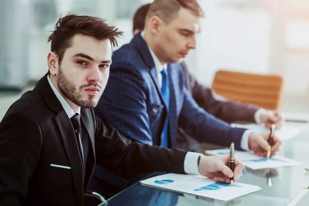 Менеджер по финансам и бизнес-команда работают с финансовыми диаграммами на своем столе в офисе.