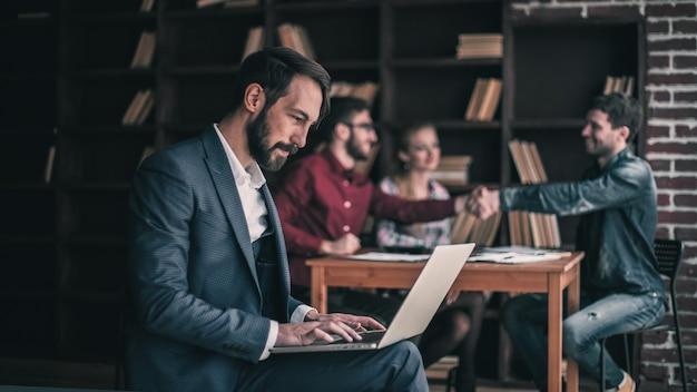 Manager financeは、オフィスの職場でビジネスパートナーがハンドシェークをしている背景で、ラップトップのマーケティンググラフィックを操作します。