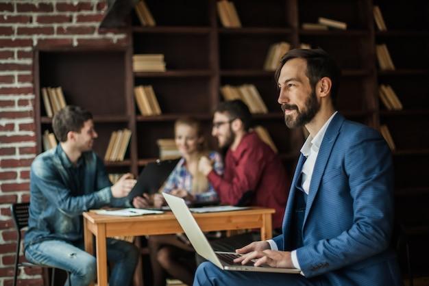 재무 관리자는 사무실에서 비즈니스 팀 직장의 배경에 노트북의 마케팅 그래픽과 함께 작동합니다.
