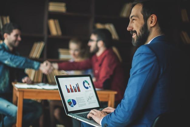 Manager financeは、オフィスのビジネスチームの職場でラップトップのマーケティンググラフィックを操作します