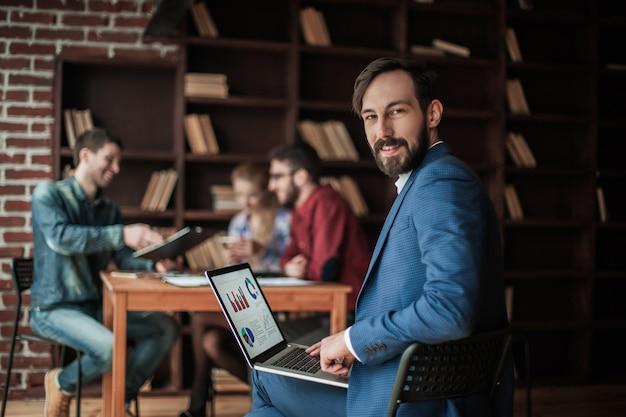 Менеджер по финансам работает с маркетинговой графикой на ноутбуке.