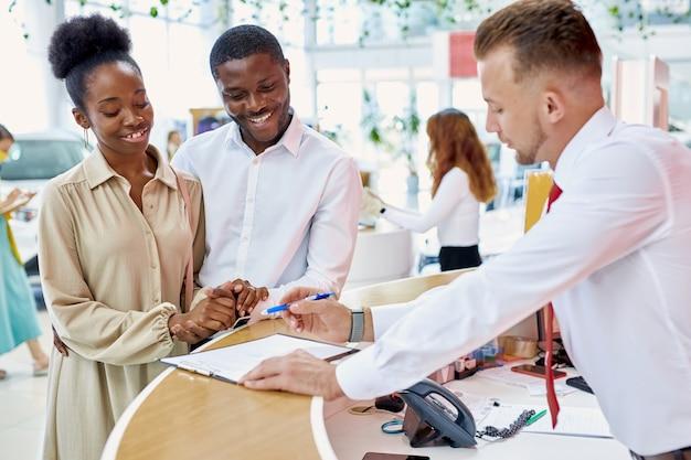 매니저는 대리점에서 고객에게 서명하기 위해 자동차 판매 계약을 제공합니다.