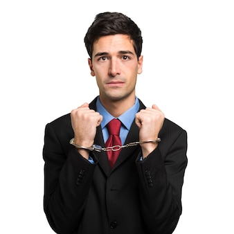Manager in handcuffs in his office looking sad