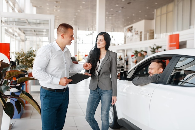 Manager and happy couple near the new car in showroom.