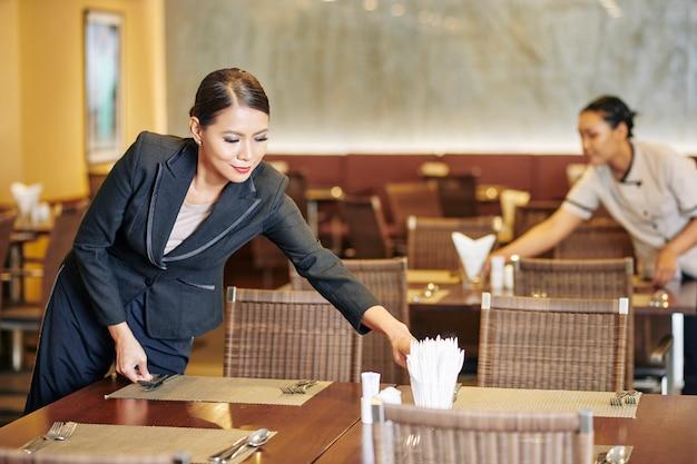 Менеджер помогает официантке в ресторане