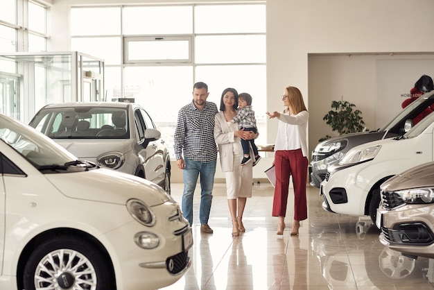 The manager helps the young family choose the most comfortable car for the city.