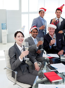 Manager and his team with novelty christmas hat toasting at a party