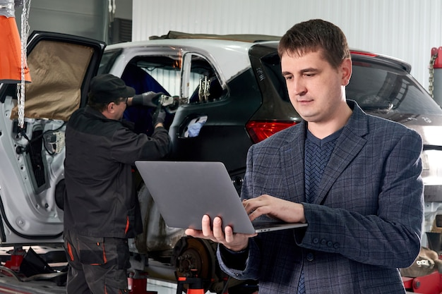 Менеджер держит ноутбук, стоя возле машины в автосервисе с механиком, ремонтирующим автомобиль на заднем плане