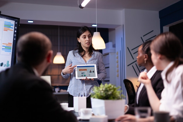 Manager holding tablet pc in meeting room late at night